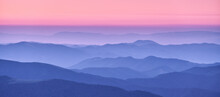 Mountain Ridges In Fog And Pink Sky At Sunset In Autumn. Beautiful Landscape With Foggy Mountain Valley, Hills, Forest At Dusk In Blue Hour In Fall. Aerial View Of Hills. Top View. Nature Background