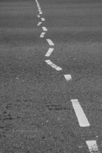 Vertical Shot Of Wiggly Traffic Lines On An Asphalt Road