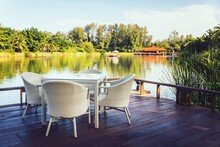 Empty Chairs And Table By Lake Against Trees