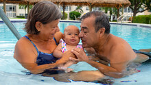 Grandparents With Granddaughter In The Pool
