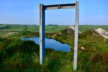Metal Frame On Top Of Hill Overlooking Lake And Backed By Blue Sky