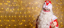 Portrait Of An Angry Santa Claus Wearing Glasses With White Long Beard Showing Middle Finger Marks Against A Wall Background With Garland. A Man In Costume Of A Fairytale Hero Shows A Finger Gesture