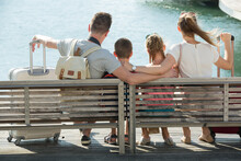 Back View Of Traveling Happy Family Of Four Relaxing On Embankment With Suitcases