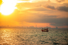 A Small Fisherman Boat Floats Alone In The Sea In The Morning Against The Backdrop Of A Big City.