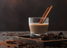 Irish Cream Baileys Liqueur In Crystal Glass With Cinnamon, Coffee Beans And Powder With Dark Chocolate In Wooden Tray On Dark Wood Background.