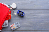 Pulse oximeter with first aid kit and pills on dark wooden background