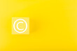 canvas print picture - Minimal trendy copyright, intellectual property and patenting concept. Copyright symbol on yellow block against yellow background with copy space
