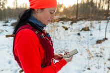 Woman Checking Mobile While Running In Woods. Female Runner Holding Cellphone In Hands On Cold Winter Day.