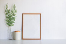 A Brown Blank Frame With Fern Over The White Background.