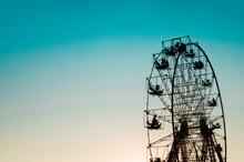 Ferris Wheel Silhouette Against Clear Blue Orange Sky