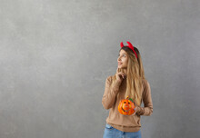 Girl With Dreamy Expression Looks Away While Standing On Gray Background With Pumpkin In Her Hands. Cute Girl In Casual Clothes And With Red Devil Horns Looking Thoughtfully At Copy Space. Banner.