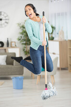 Happy Woman Cleaning And Jumping With Mop