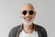Bald european man in sunglasses laughing and looking at camera