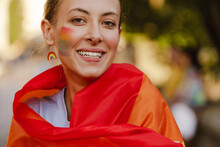White Woman With Rainbow Flag Smiling During Pride Parade