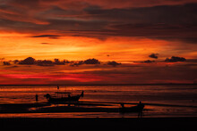 Silhouette Shot Of Boats Moored On The Seashore With Breathtaking Sunset