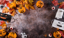 Halloween Decorations Made From Pumpkin, Paper Bats,medical Mask And Black Spider On Dark Stone Background. Flat Lay, Top View With Copy Space For Text.