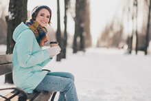 Profile Side Photo Of Attractive Cheerful Young Woman Sit Bench Cold Snow Weather Smile Drink Coffee Outdoors Outside