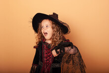 A Little Girl Holds A Huge Spider In A Witch Costume For Halloween Scares Opening Her Mouth At A Holiday Party With A Place For Text