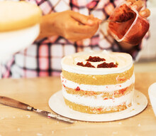 Young Woman Confectioner In An Apron Greases The Cake With Jam. Delicious Pastries. Hobby. Small Home Business.