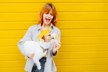 Red Head Hair Woman With Surprise Upset Emotion And Is Holding An Ice Cream In Her Hand That The Pet Licks Next To Yellow Wall In The Summer, Outdoor. Pet Lover, Animal And People Concept.