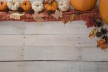 Rustic Autumn Background With Orange And White Pumpkins,  Leaves, Pine Cones, Acorns And A Plaid Cloth.  Copy Space.