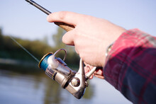 Spinning Fishing. Male Hands Holding A Spinning Rod On The Background Of A Lake On An Autumn Sunny Day, Close-up, Soft Focus.