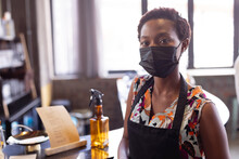 Portrait Of African American Woman Wearing Apron And Face Mask Standing At Gin Distillery