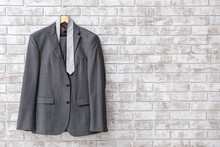 Hanger With Stylish Suit And Necktie Hanging On Brick Wall