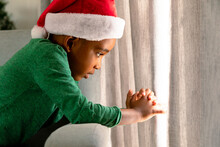 African American Boy Wearing Santa Hat And Looking Through Window At Christmas Time