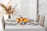 Stylish served table with autumn decor in room