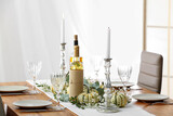 Beautiful table serving with autumn decor, bottles of wine and candles in light room