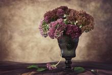 Pink Autumn Flowers In A Dark Wineglass On Grunge Background