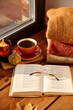 Leinwandbild Motiv season and objects concept - open book with glasses, cup of coffee, autumn wool sweaters, pumpkin and candle burning on wooden window sill at home