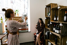 Two Female Wine Lovers Take Picture Selfie With A Tablet In A Wine Shop - Bloggers Vloggers Posting On Social Networks During Wine Tasting