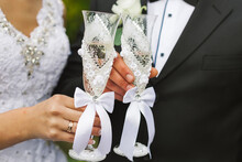 Bride And Groom Keep Two Glasses Of Champagne Decorated With White Flowers