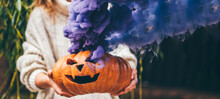 Woman Holding Halloween Pumpkin. Halloween Orange Pumpkin Smoking With Purple Smoke.