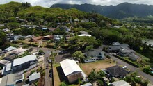 Drone Flying Over Beautiful Kaneohe Neighborhood On Oahu In Hawaii, With Mountain Range In The Distance