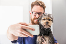 Smiling Veterinarian Taking Selfie With Yorkshire Terrier