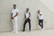 Black Male Friends In Stylish Outfits Standing Near Concrete Wall
