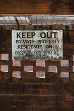 Keep Out, Private Property Sign On An Old Brick Wall In A Car Port.