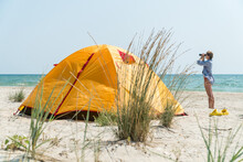 Woman Looking Through Binoculars On A Sea Beach In Front Of A Yellow Tent.