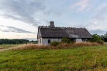 An Old Abandoned House With A Thatched Roof, Solitary Located Close To The Sea