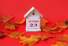 Calendar For October 23 : Decorative House With The Name Of The Month In English, The Number 23, Autumn Maple Leaves On A Red Background, Side View