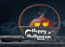Carved Halloween Pumpkin Jack O Lantern In A Basket On A Rustic Wooden Table With A Butcher Cleaver