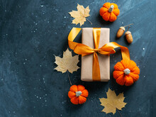 Halloween Sale Concept Or Gift Box For Thanksgiving. A Gift With An Orange Ribbon On A Dark Table With Maple Leaves And Knitted Pumpkins Copy Space