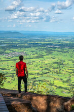 Working Young Man Standing On Top Of Cliff In Summer Mountains At Enjoying View Of Nature, At Pha Chom Tawan In Phu Wiang National Park, Khon Kaen, Thailand.