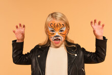Angry Girl With Tiger Face Painting Growling And Showing Scary Gesture Isolated On Beige