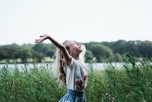 Girl Dancing In Nature Looking Up The The Sky Enjoying The Sunshine