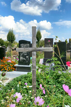 Old Wooden Crosse And Different Graves On Rustic Orthodox Or Catholic Cemetery. Flowers On Tombstones. Medium Plan.