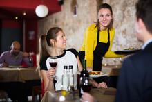 Polite Waitress Bringing Ordered Dishes To Family Couple At Restaurant